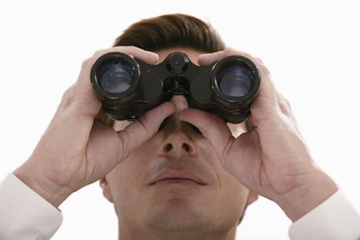 Businessman looking through binoculars : Stock Photo