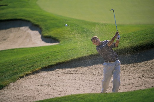 Man hitting golf ball out of sand trap : Stock Photo