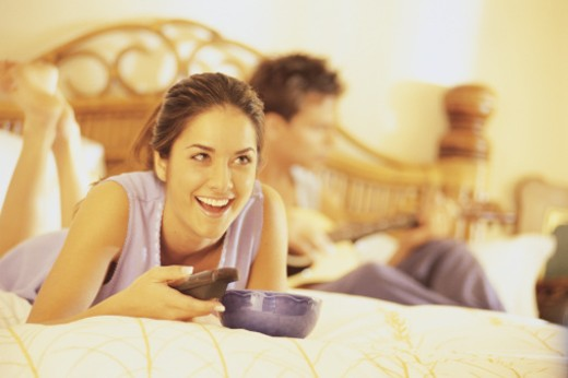 Woman on bed watching TV : Stock Photo