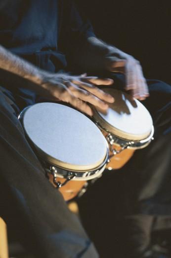 Hands playing bongos : Stock Photo
