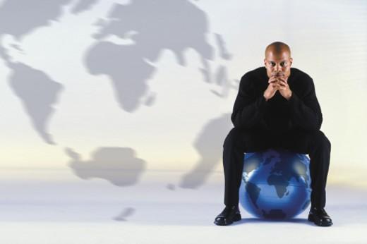 Stock Photo: 1557R-0622 Man sitting on a globe