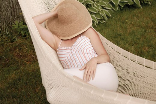 Stock Photo: 1557R-0843 Woman in hammock with hat covering her face