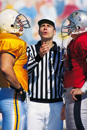 Stock Photo: 1557R-164098 Referee flipping coin at start of football game