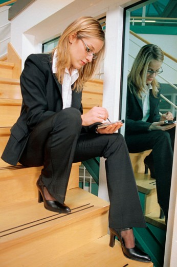 Woman with PDA sitting on stairs : Stock Photo