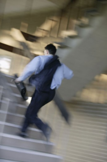 Businessman running up stairs : Stock Photo