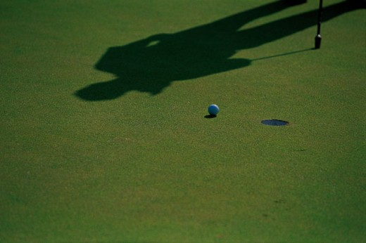 Stock Photo: 1557R-277106 Shadow of golfer on putting green with ball and hole