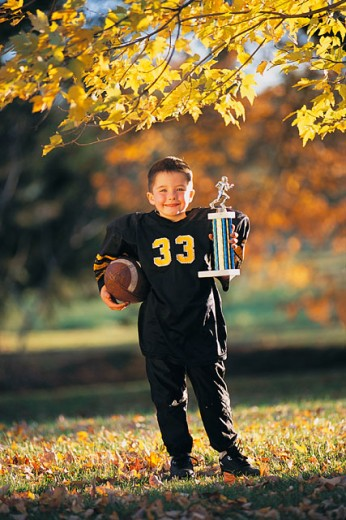Boy with football and trophy : Stock Photo