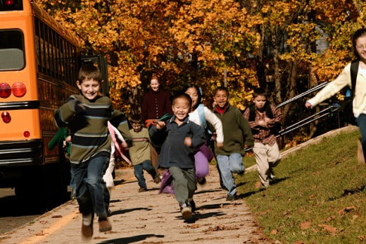 Children running after getting off school bus : Stock Photo