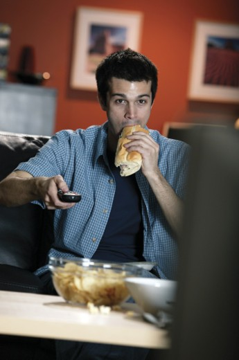 Man eating sandwich while watching TV : Stock Photo