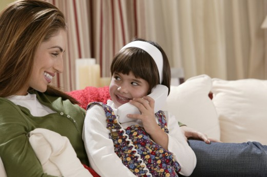 Mother with daughter talking on telephone : Stock Photo