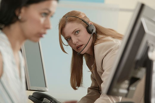 Telemarketer looking at colleague in frustration : Stock Photo