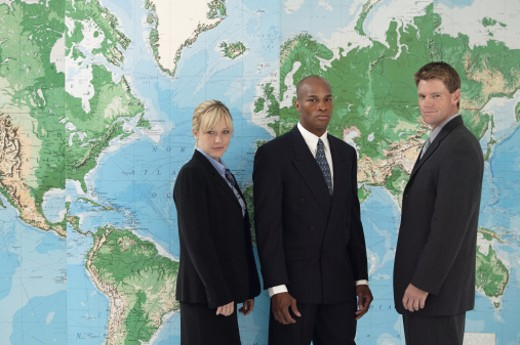 Stock Photo: 1557R-278275 Business colleagues in suits against world map
