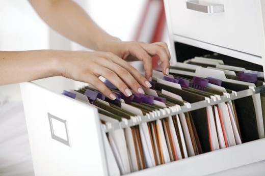 Woman's hands going through files in cabinet : Stock Photo