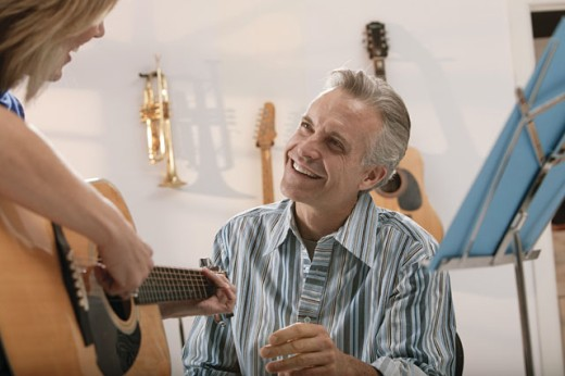 Man giving guitar lesson : Stock Photo