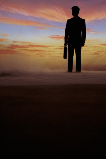 Stock Photo: 1557R-279820 Silhouette of businessman on horizon