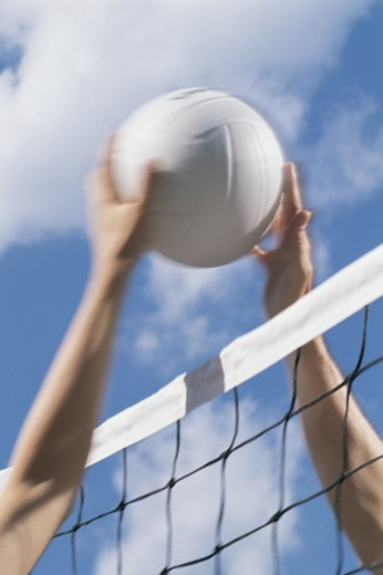 Arms of volleyball players meet at ball over net : Stock Photo
