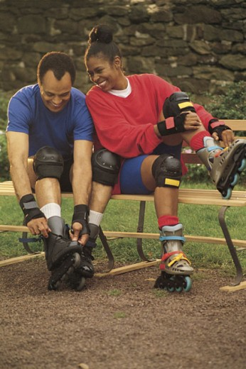 Couple putting on inline skates : Stock Photo
