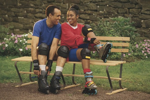 Couple in park putting on inline skates : Stock Photo
