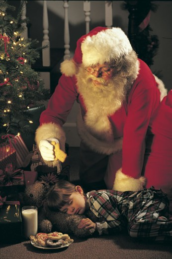 Santa Claus reaching over sleeping child for a snack : Stock Photo