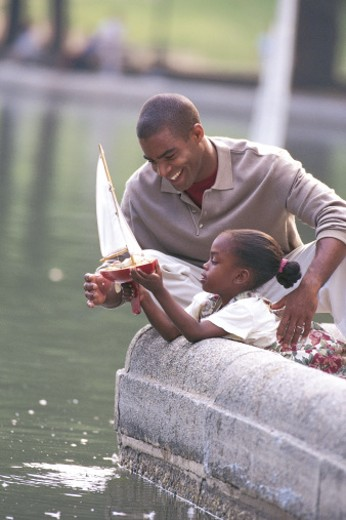 Stock Photo: 1557R-281220 Father and daughter with toy boat at park reservoir