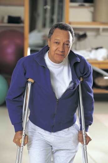 Stock Photo: 1557R-281233 Man on crutches posing