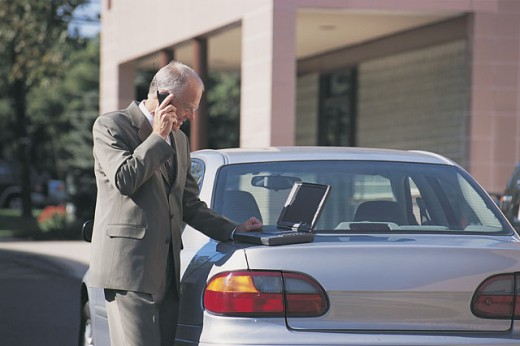 Man on cell phone using laptop on trunk of car : Stock Photo