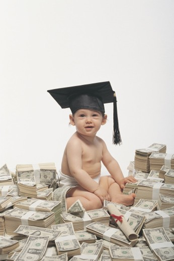 Baby sitting atop heap of cash wearing graduation cap : Stock Photo