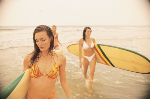 Stock Photo: 1557R-282440 Women carrying surfboards on beach