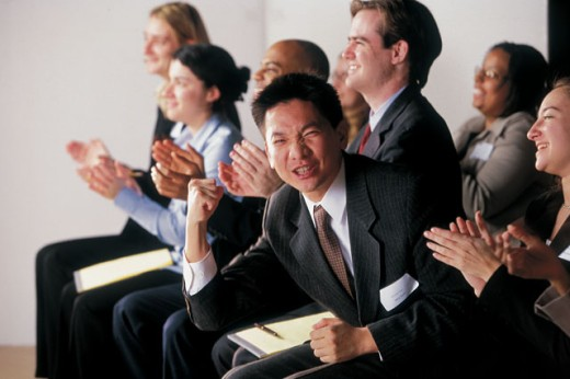 Excited businessman among clapping audience : Stock Photo