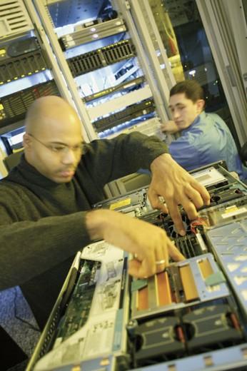 Computer technician working in server room : Stock Photo