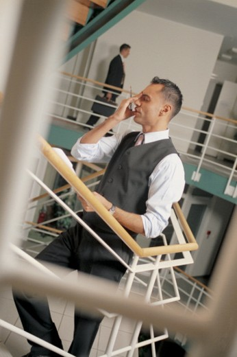 Businessman using cell phone on staircase : Stock Photo