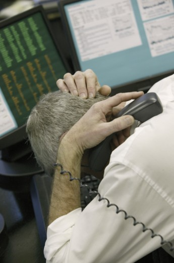Man at computer holding telephone : Stock Photo