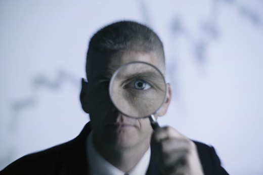 Man holding magnifying glass to his eye : Stock Photo