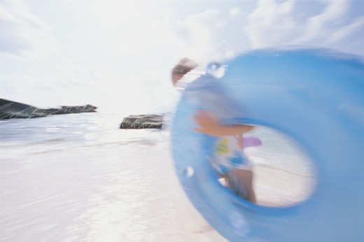 Girl at beach running with inner tube : Stock Photo