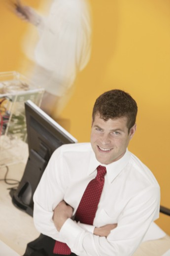 Businessman posing by flat panel monitor : Stock Photo