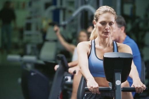 Woman on exercise machine : Stock Photo