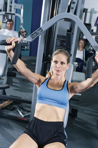 Woman on exercise machine : Stock Photo