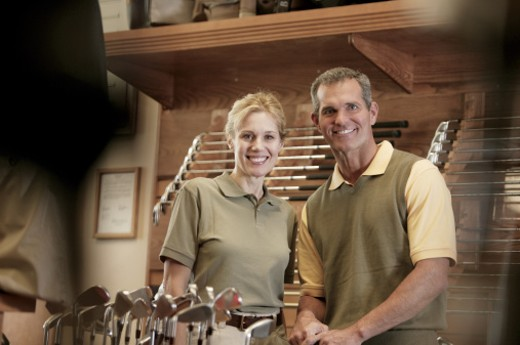 Man and woman at golf equipment store : Stock Photo