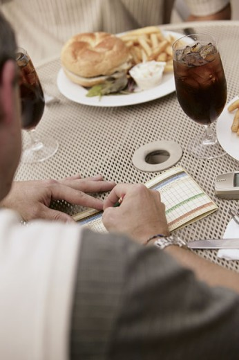 Man filling out golf score card while eating : Stock Photo