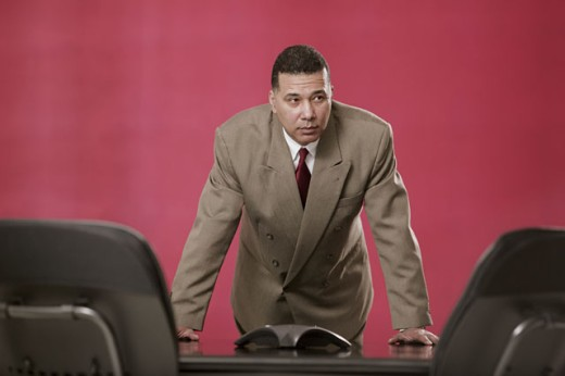 Businessman standing by conference table : Stock Photo
