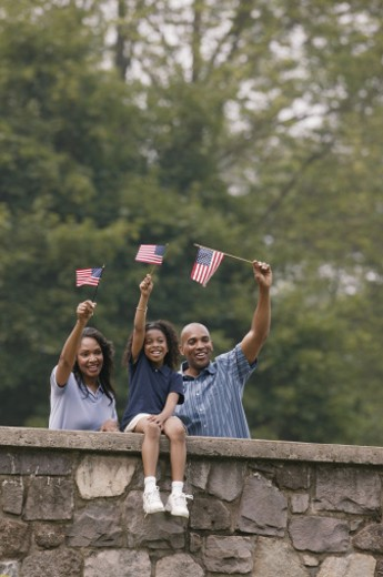 Family waving American flags outdoors : Stock Photo
