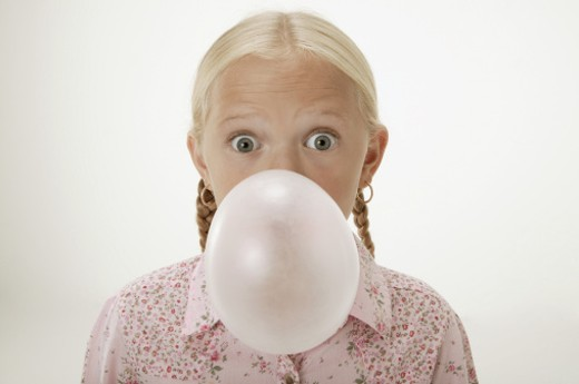 Girl blowing bubble with gum : Stock Photo
