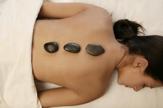 Woman getting hot stone massage : Stock Photo