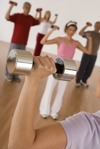 Woman lifting dumbbell in exercise class : Stock Photo