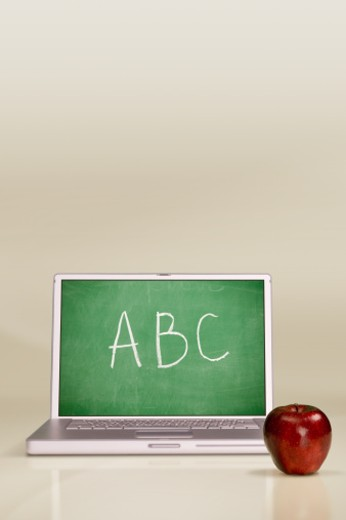 Laptop computer with chalkboard on screen and apple : Stock Photo