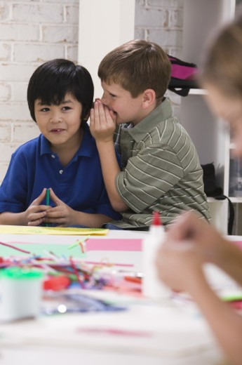Boys whispering in classroom : Stock Photo