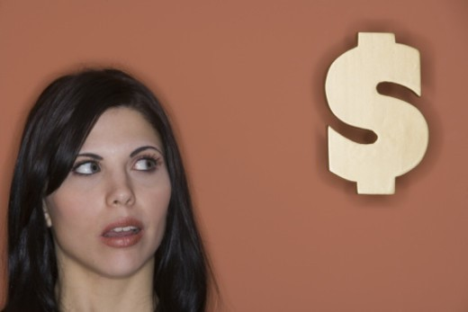 Woman looking at dollar sign : Stock Photo