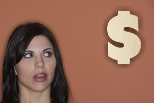 Stock Photo: 1557R-297609 Woman looking at dollar sign