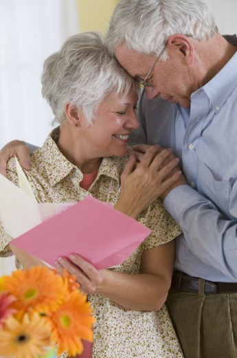 Couple embracing and reading a card : Stock Photo