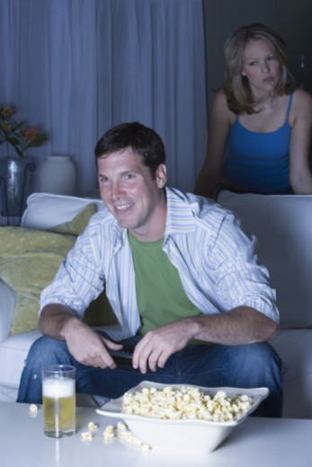 Man watching television with upset woman standing behind him : Stock Photo